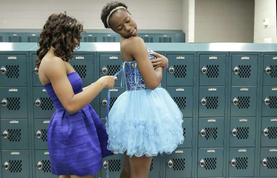 Aisha Harris ties the back of a dress of classmate Amie Johnson, as they try on dresses during the Project Prom distribution at Pin Oak Middle School on Saturday, April 7, 2018, in Bellaire. Over 900 HISD students were able to select prom attire at no cost during the event. ( Elizabeth Conley / Houston Chronicle ) Photo: Elizabeth Conley, Chronicle / Houston Chronicle / © 2018 Houston Chronicle