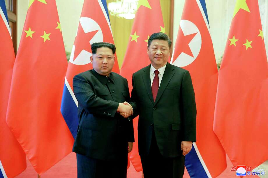 "FILE - In this March 26, 2018, file photo, North Korean leader Kim Jong Un, left, and Chinese counterpart Xi Jinping, shake hands at the Great Hall of the People in Beijing. As the U.S.-North Korea summit looms, President Donald Trump's policy of maximum pressure on North Korea may be working - thanks to China. Beijing appears to have gone well beyond U.N. sanctions on its unruly neighbor, reducing its total imports from North Korea in the first two months this year by 78.5 and 86.1 percent in value. The content of this image is as provided and cannot be independently verified. Korean language watermark on image as provided by source reads: ""KCNA"" which is the abbreviation for Korean Central News Agency. (Korean Central News Agency/Korea News Service via AP, File) / KCNA via KNS"