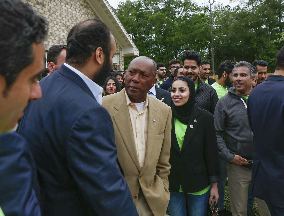 Houston Mayor Sylvester Turner and Crown Prince Mohammed bin Salman talk in front of a Habitat for Humanity home on Saturday, April 7, 2018, in Houston.