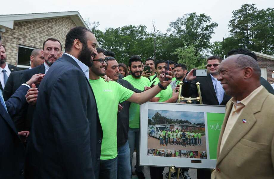 Houston Mayor Sylvester Turner (right) watches a volunteer take a selfie with His Royal Highness Crown Prince Mohammed bin Salman talk in front of a Habitat for Humanity home Saturday, April 7, 2018, in Houston. His Royal Highness Crown Prince Mohammed bin Salman visited a habitat for humanity home that aided Harvey victims and was supported by donations by the Aramco, the Saudi oil company. ( Steve Gonzales / Houston Chronicle ) Photo: Steve Gonzales, Houston Chronicle / Houston Chronicle / © 2018 Houston Chronicle