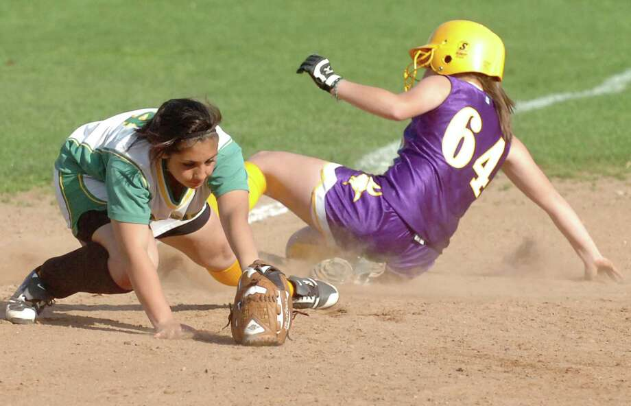 Westhill's Cassandra Kish slides safely into third as Trinity's Krissy Schule covers the base during the Vikings' 4-0 win on April 8, 2010. Photo: Keelin Daly / File Photo / Stamford Advocate