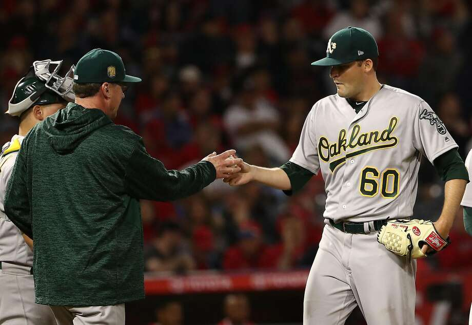 ANAHEIM, CA - APRIL 07: Pitcher Andrew Triggs #60 of the Oakland Athletics hands to ball to manager Bob Melvin as Melvin takes out Triggs in the sixth inning during the MLB game against the Los Angeles Angels of Anaheim at Angel Stadium on April 7, 2018 in Anaheim, California.  (Photo by Victor Decolongon/Getty Images) Photo: Victor Decolongon / Getty Images