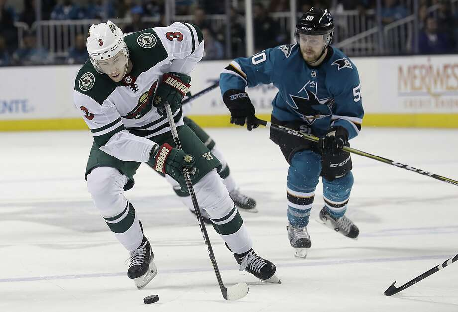 Minnesota center Charlie Coyle skates in front of San Jose center Chris Tierney in the first period Saturday. Photo: Jeff Chiu / Associated Press
