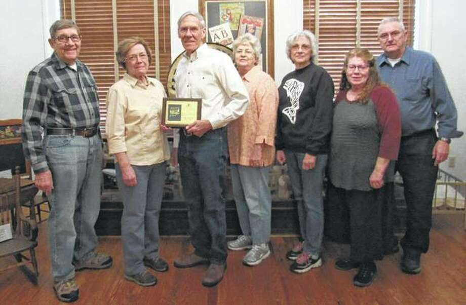 "Greene County Historical and Genealogical Society recently received the 2016 Excellence Award from Acclaim Press for its ""Greene County, Illinois, History and Families"" book that was published in September 2016. Criteria for the award, presented by Douglas Sikes of Acclaim Press, included aesthetic appeal, literary content and commercial success. Historical society members on hand to accept the award included Larry Gillingham (from left), Terry Kruckeberg, President Steve Black, Margaret Camerer, Mary Varble, Jean Coates and Gary Coates. Black noted that more than 500 families helped to make the book by submitting stories and histories relating to their ancestors. Copies of the book are available for $65 at the GCHGS office in Carrollton. Photo: Photo Provided"