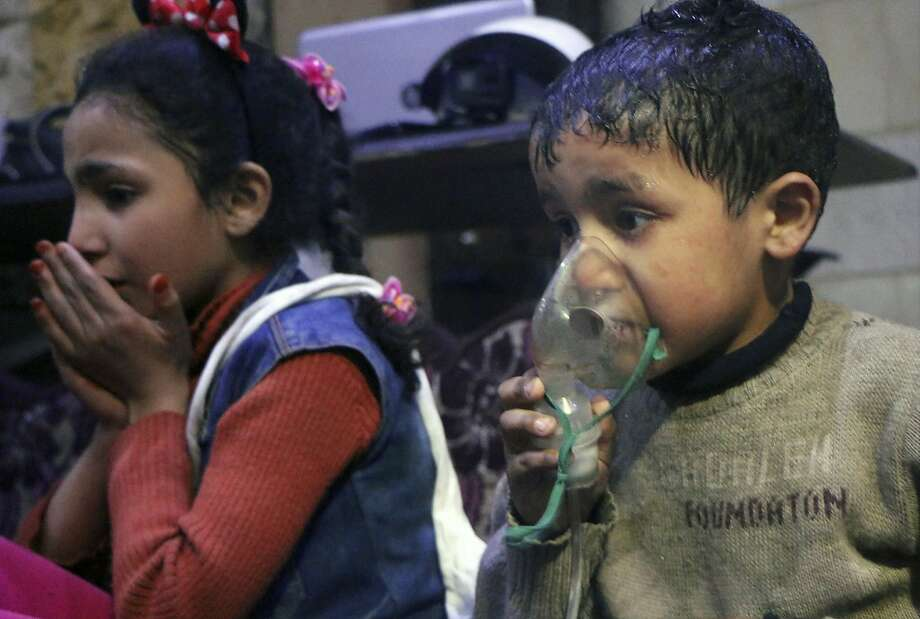This image released early Sunday, April 8, 2018 by the Syrian Civil Defense White Helmets, shows a child receiving oxygen through respirators following an alleged poison gas attack in the rebel-held town of Douma, near Damascus, Syria. Syrian rescuers and medics said the attack on Douma killed at least 40 people. The Syrian government denied the allegations, which could not be independently verified. The alleged attack in Douma occurred Saturday night amid a resumed offensive by Syrian government forces after the collapse of a truce. (Syrian Civil Defense White Helmets via AP) Photo: Associated Press