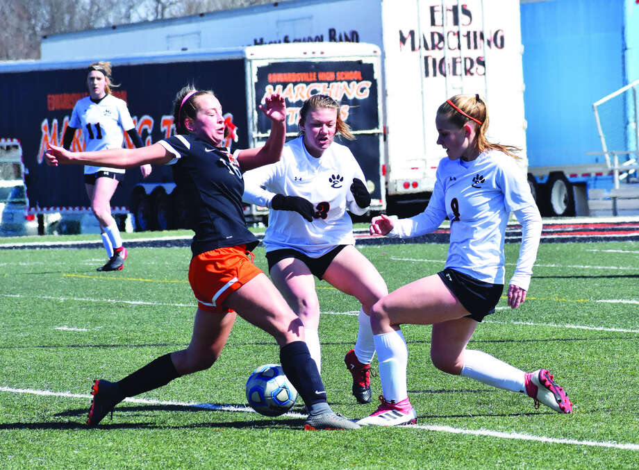 Normal Community's Megan Seger, left, battles with Edwardsville's Casey Hansen, center, and Sarah Kraus for a loose ball in the first half of Saturday's non-conference game.