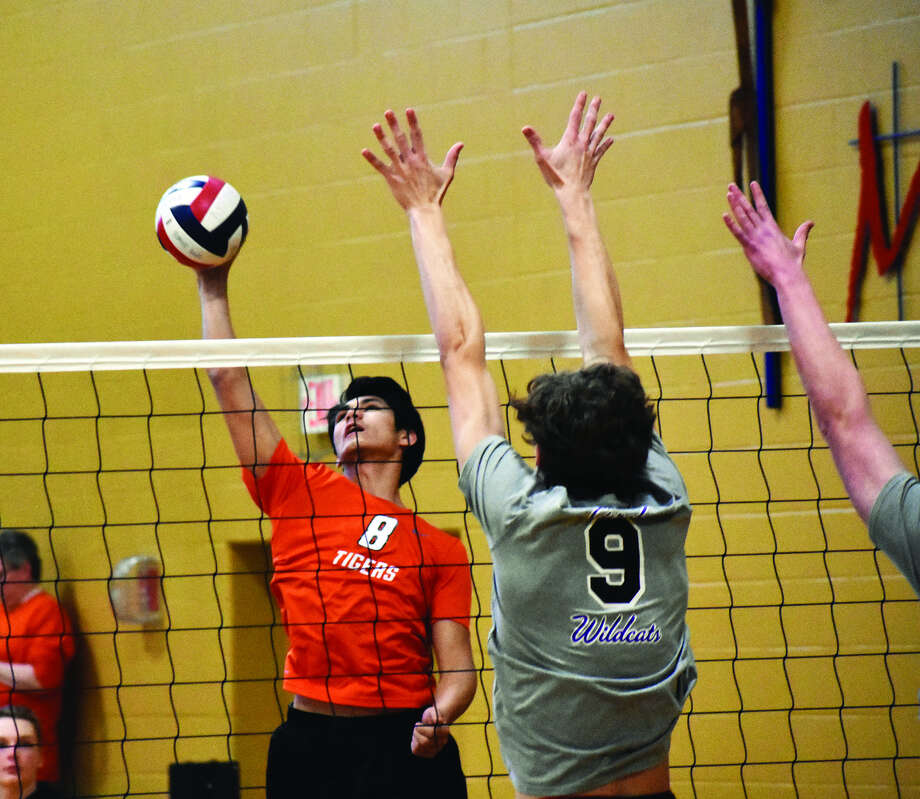 Edwardsville hitter Eric Epenesa, left, goes up for a kill attempt against two Eureka blockers during the first game of a match to determine the third seed in the Vianney Tournament.