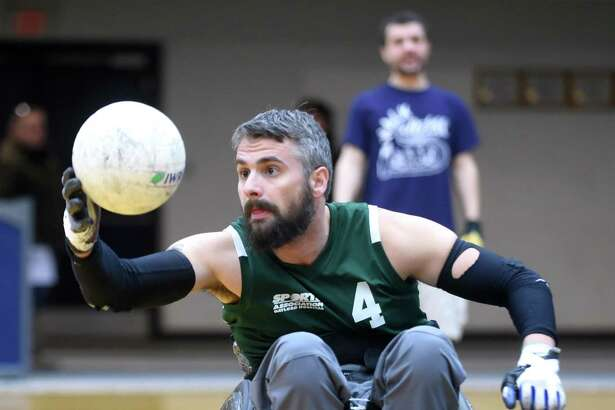 Brett Smith of the Connecticut Jammers Quad Rugby Team catches a pass during a wheelchair rugby demonstration and clinic at the Adaptive Sports Fest at Southern Connecticut State University's Moore Field House in New Haven on Saturday.