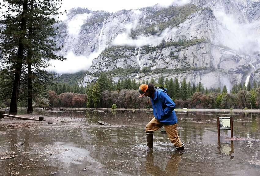 Kevin Kimo Laughlin, a maintenance worker for Aramark, wades back to dry ground as the Merced River rises due to rain in Yosemite National Park's Yosemite Valley on Saturday, April 7, 2018. Northern California was drenched by a powerful