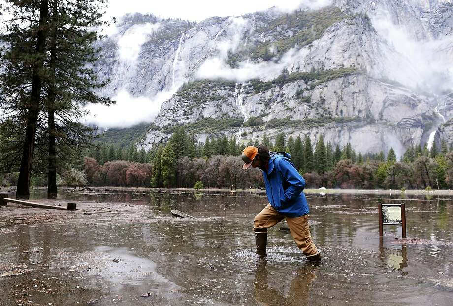 Kevin Kimo Laughlin wades to dry ground as the Merced River rises in Yosemite Valley on Saturday. Waters receded on Sunday. Photo: Eric Paul Zamora / Fresno Bee