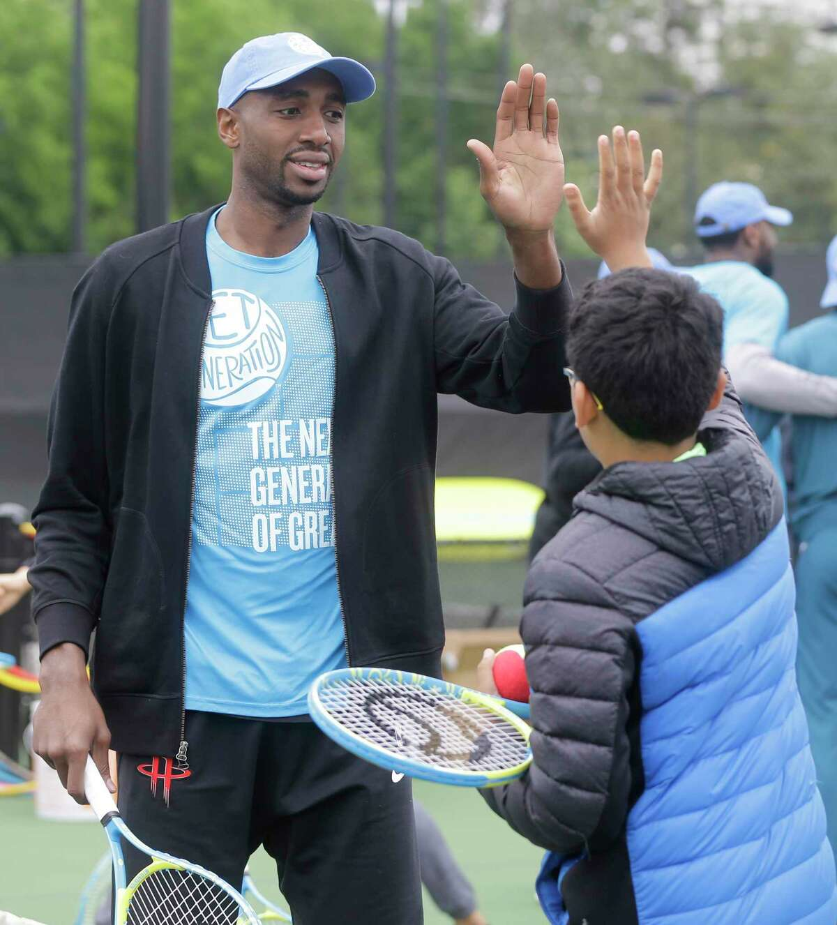 Houston Rockets player Luc Mbah a Moute gives a high five to Nishant Revanur, 12, of Sugar Land at the Kids Day event during the U.S. Men's Clay Court Championship at River Oaks Country Club, 1600 River Oaks Blvd., Sunday, April 8, 2018, in Houston.
