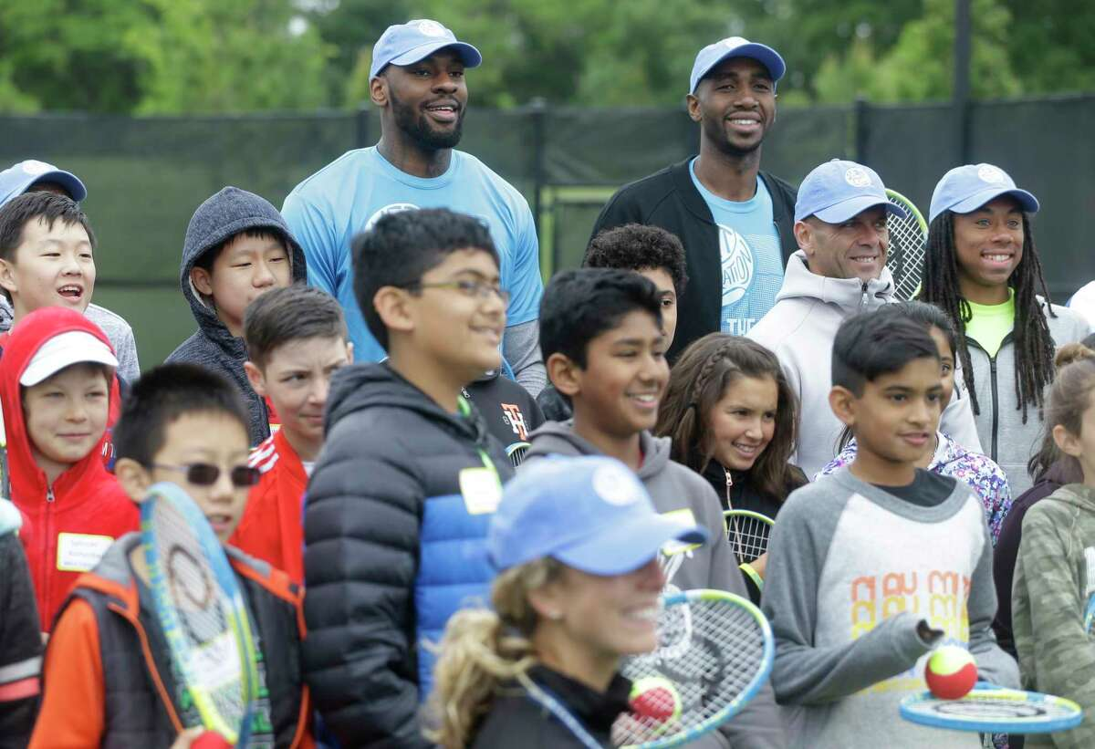 Houston Rockets players Tarik Black, left, and Luc Mbah a Moute, right, pose with participates of the Kids Day event during the U.S. Men's Clay Court Championship at River Oaks Country Club, 1600 River Oaks Blvd., Sunday, April 8, 2018, in Houston.