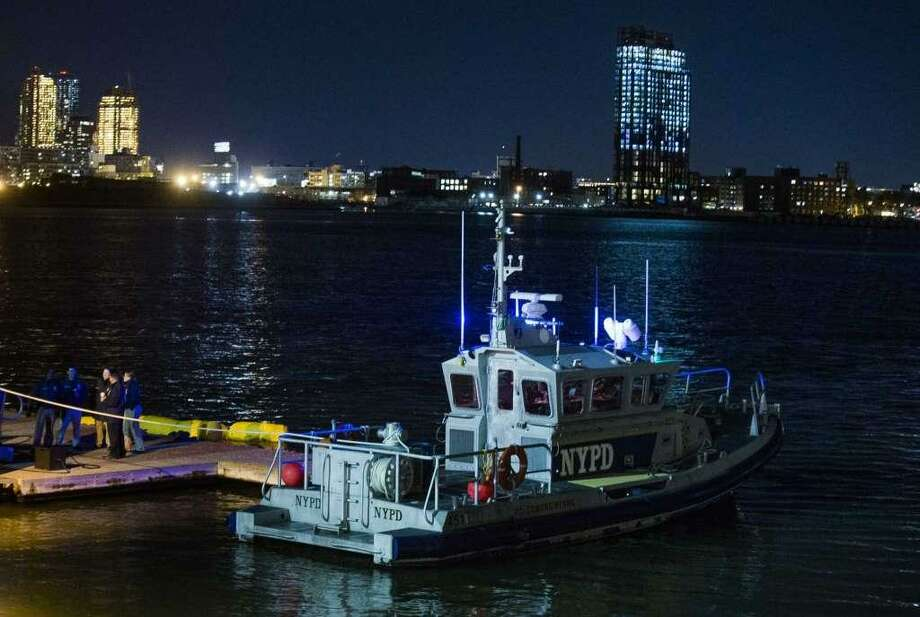 Yellow buoys that a New York police officer said are suspending a helicopter that crashed on the East River float next to a NYPD police boat at a pier in New York on Sunday, March 11, 2018. The helicopter crashed into New York City's East River Sunday night and flipped upside down in the water, killing at least a few people aboard and leaving some others in critical condition, officials said. Photo: /