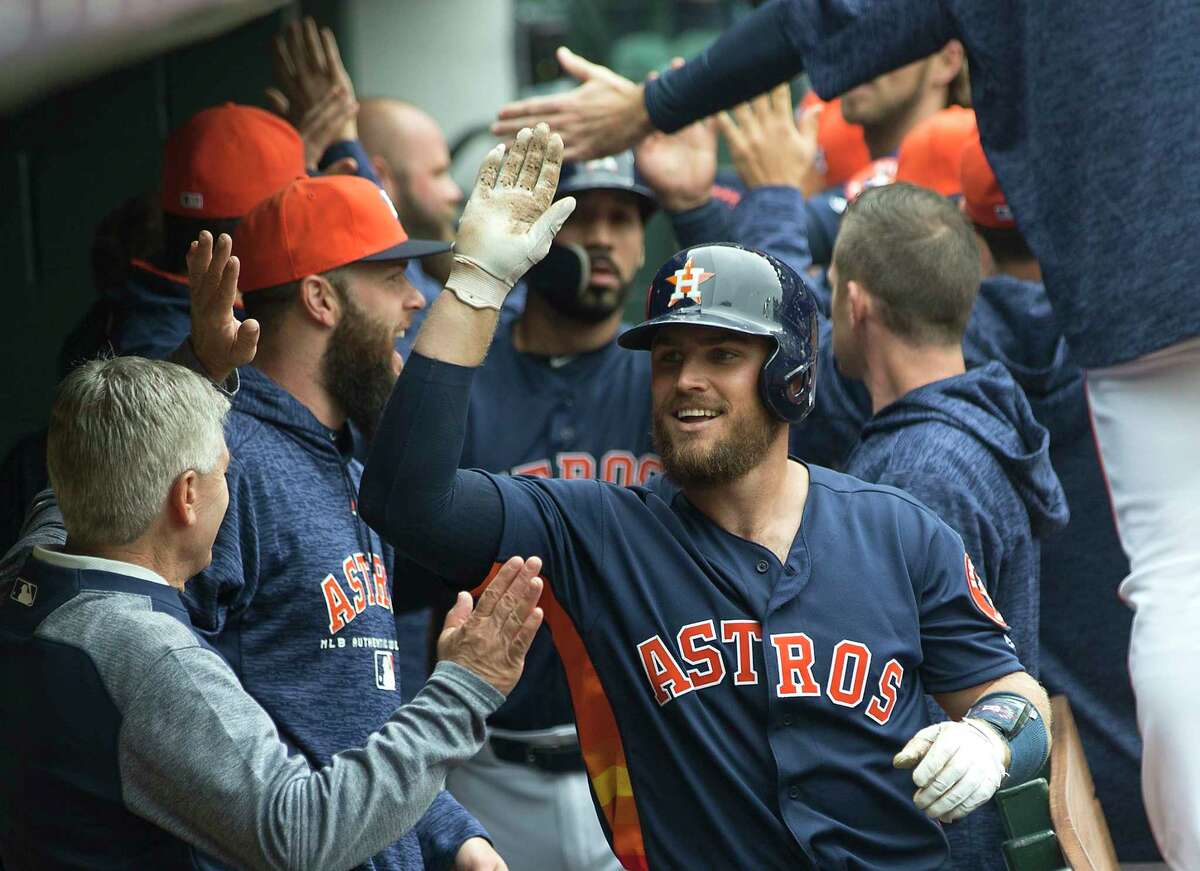Houston Astros catcher Max Stassi (12) high fives his teammates in the dugout after hitting a 3-run home run off of San Diego Padres starting pitcher Tyson Ross during the fifth inning of a major league baseball game at Minute Maid Park on Sunday, April 8, 2018, in Houston.