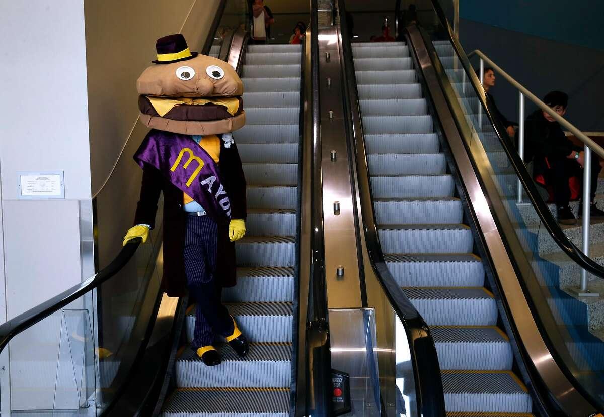 Mayor McCheese (Kishore Hari) rides an escalator at the Silicon Valley Comic Con in San Jose, Calif. on Saturday, April 7, 2018.