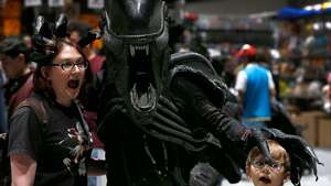 Leah Jarvis and her son Evan, 7, have an encounter with the Alien (Matthew O�Connor) at the Silicon Valley Comic Con in San Jose, Calif. on Saturday, April 7, 2018.