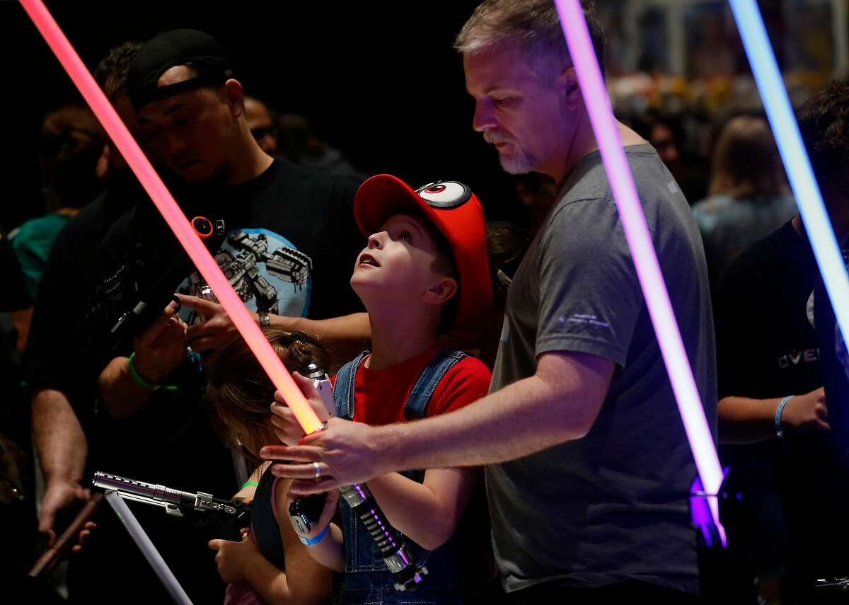 Nathan Criswell, 10, admires light sabers offered for sale with his father Brice at the Silicon Valley Comic Con in San Jose, Calif. on Saturday, April 7, 2018.