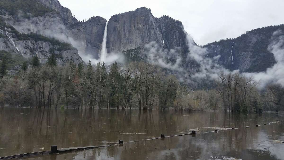 In this Saturday, April 7, 2018 photo released by the National Park Service, floodwaters cover Cooks Meadow and the pedestrian trail through Cooks Meadow in Yosemite Valley in Yosemite, Calif. Sections of Northside Drive, Southside Drive, and Sentinel Drive remain closed due to high water in the roadway. Parts of Yosemite National Park remained closed as the Merced River peaked several feet above flood stage through the Yosemite Valley. (National Park Service via AP)