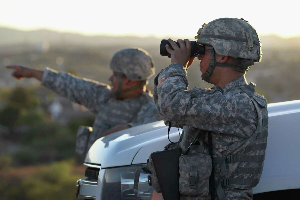 FILE PHOTO: U.S. Army National Guardsmen scan the U.S.-Mexico border on June 22, 2011 in Nogales, Arizona.