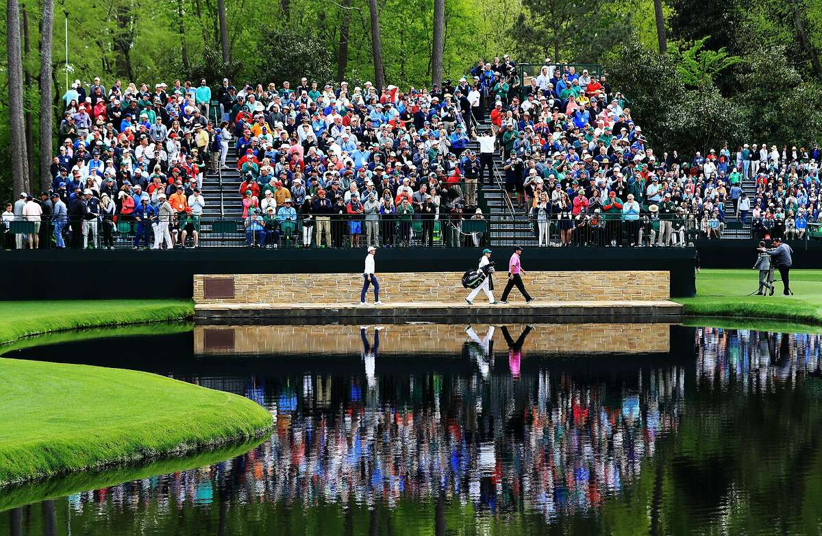 AUGUSTA, GA - APRIL 08: Patrick Reed of the United States, Rory McIlroy of Northern Ireland and caddie Kessler Karain cross the Sarazen Bridge on the 16th hole during the final round of the 2018 Masters Tournament at Augusta National Golf Club on April 8, 2018 in Augusta, Georgia. (Photo by Andrew Redington/Getty Images)