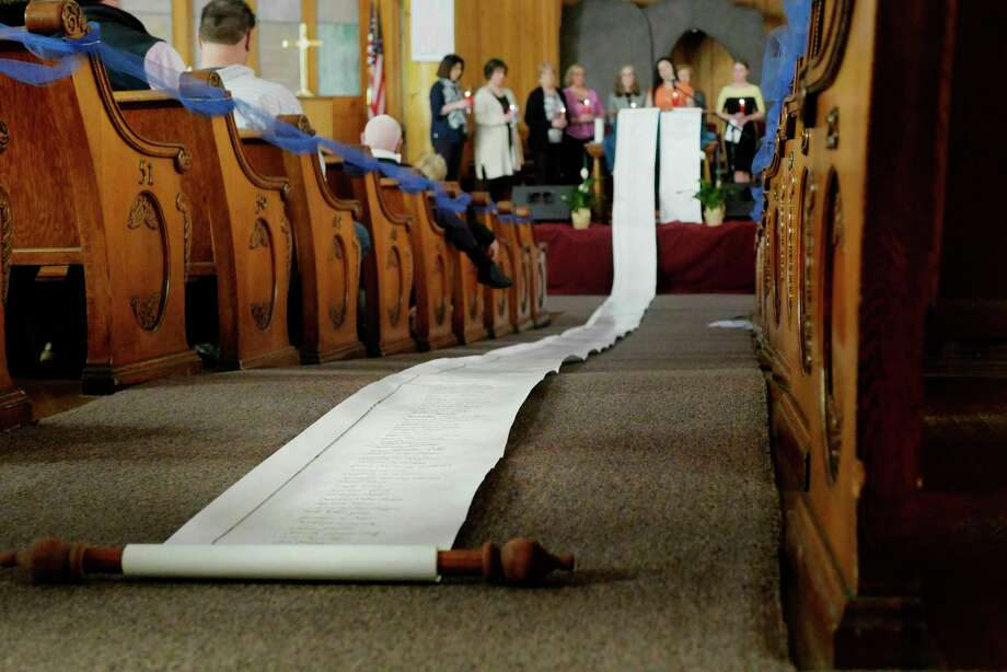 The victim's memorial scroll, containing the names of crime victims from 1996, is seen rolled out on the floor at the 19th Annual Candlelight Vigil for Victims of Crime at the First Baptist Church of Ballston Spa on Sunday, April 8, 2018, in Ballston Spa, N.Y.  (Paul Buckowski/Times Union) / (Paul Buckowski/Times Union)