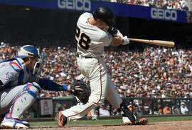 SAN FRANCISCO, CA - APRIL 08:  Buster Posey #28 of the San Francisco Giants hits an RBI single scoring Hunter Pence #8 against the Los Angeles Dodgers in the bottom of the eighth inning at AT&T Park on April 8, 2018 in San Francisco, California.  (Photo by Thearon W. Henderson/Getty Images)