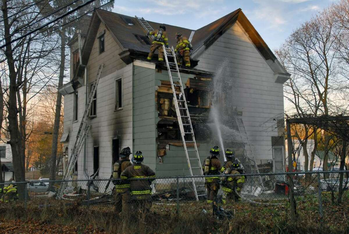 Firefighters work to extinguish the hot spots in the walls and roof of a burning home Sunday on Sheridan Avenue in Troy. (Philip Kamrass /Times Union)