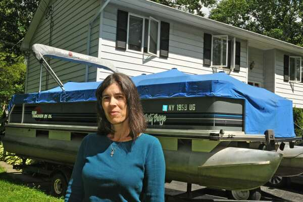 Lynda Bablin's pontoon boat is parked in her driveway near Saratoga Lake in Malta. The lake level is low. (Lori Van Buren / Times Union)