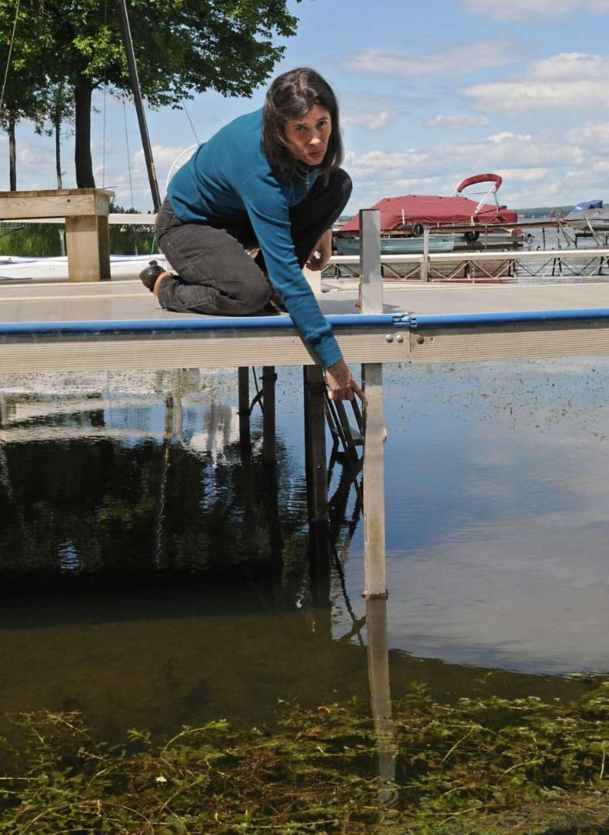 Lynda Bablin shows the normal water level on her dock on Saratoga Lake in Malta. (Lori Van Buren / Times Union)