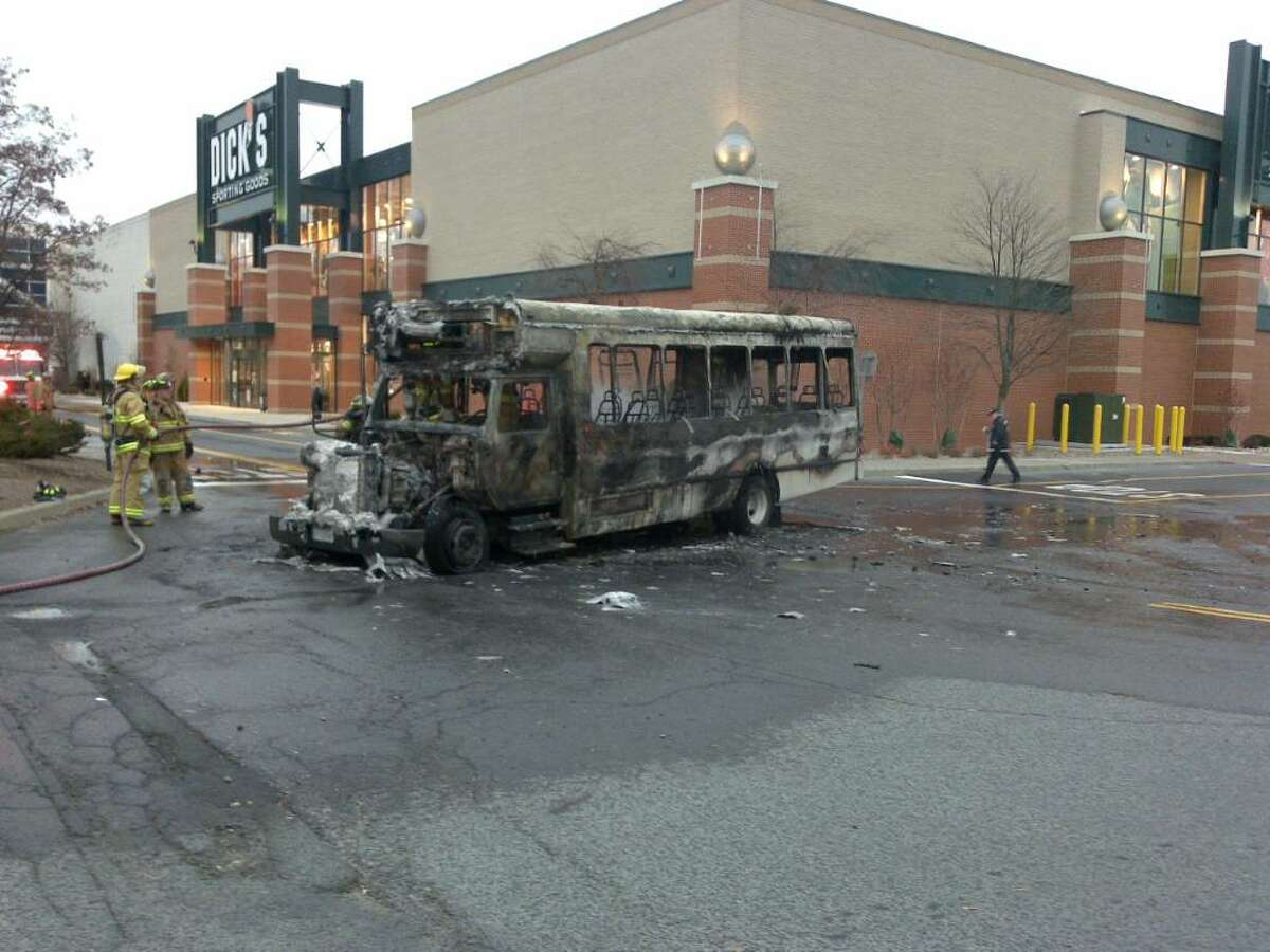 Firefighters from Guilderland pour water on a CDTA bus Monday morning. The commuter bus caught fire in the parking lot of Crossgates Mall. No one was hurt. (Guilderland Police Department)