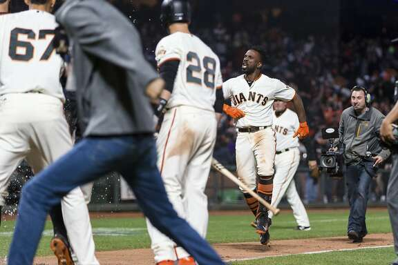 San Francisco Giants right fielder Andrew McCutchen, center right, reacts after hitting a three-run home run for a walkoff win against the Los Angeles Dodgers in the 14th inning of a baseball game in San Francisco, Saturday, April 7, 2018. (AP Photo/John Hefti)