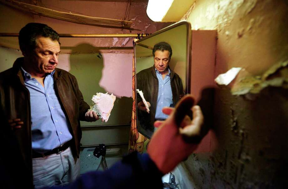FILE - In this March 12, 2018 file photo, New York Gov. Andrew Cuomo examines a damaged piece of a bathroom wall in a New York City Housing Authority (NYCHA) apartment during a tour of the Andrew Jackson Houses in the Bronx borough of New York. Cuomo recently declared a state of emergency at the New York City Housing Authority and said he would set up an independent monitor to oversee repairs after federal housing secretary Ben Carson said he would require the agency to get prior approval from the Department of Housing and Urban Development for any expenditure out of its capital fund. (James Keivom/New York Daily News via AP, Pool, File) Photo: James Keivom / Pool, The Daily News