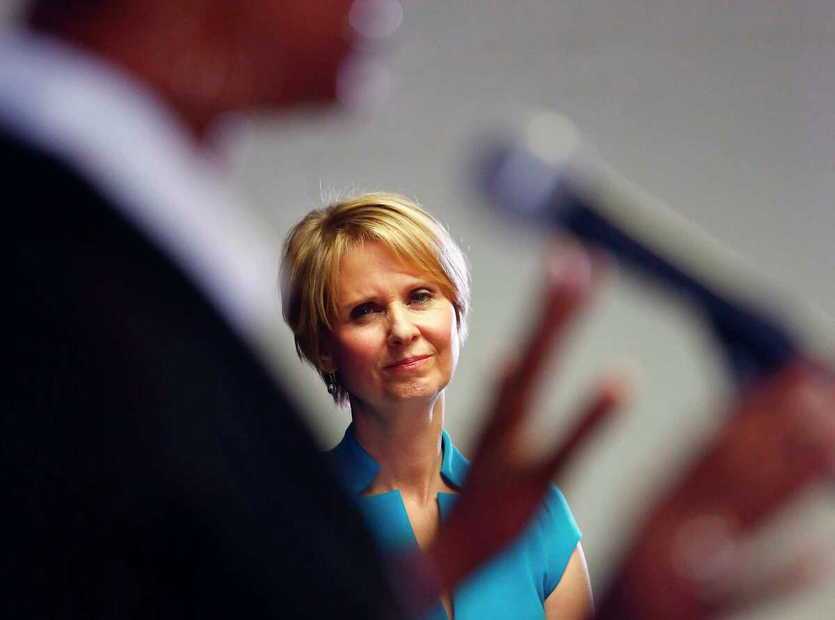 FILE - In this March 20, 2018 file photo, candidate for New York governor Cynthia Nixon, right, running against Gov. Andrew Cuomo, listens as she is introduced during a campaign stop at the Bethesda Healing Center church, in the Brooklyn borough of New York. New York City's massive public housing system is finally getting attention from politicians after years of neglect and a winter of heating failures, with both Nixon and Cuomo recently touring a public housing complex in Brooklyn. (AP Photo/Bebeto Matthews, File)