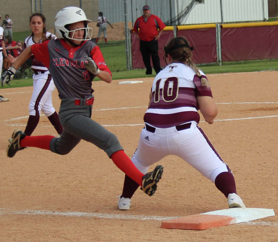 Cleveland Lady Indian Caitlyn Meshell (left) is inches away from reaching first base, which is guarded by Tarkington LadyHorn Kaycie Burns (10) during the April 3 softball game. Photo: Jacob McAdams