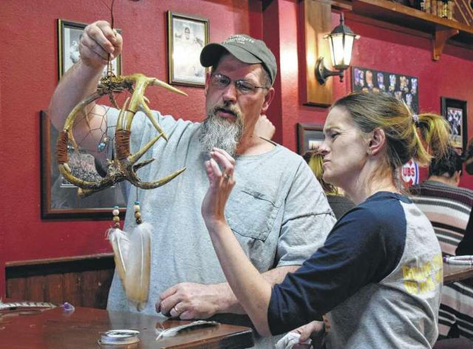 Donnie Littler of Jacksonville, left, and Allison Pratt look over his dreamcatcher made of antlers. Photo: Audrey Clayton | Journal-Courier