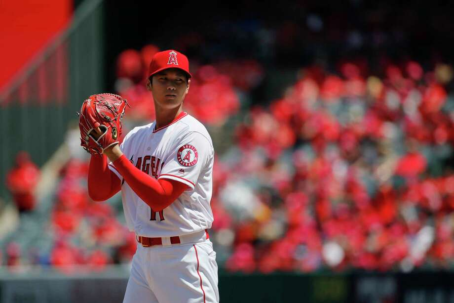Los Angeles Angels starting pitcher Shohei Ohtani, of Japan, reads the sign while throwing against the Oakland Athletics during the first inning of a baseball game, Sunday, April 8, 2018, in Anaheim, Calif. (AP Photo/Jae C. Hong) Photo: Jae C. Hong, Associated Press / Copyright 2018 The Associated Press. All rights reserved.