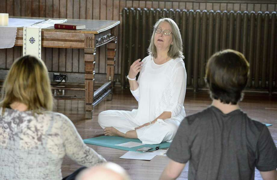 Rev. Gena Davis, an ordained Episcopal priest, begins with a spiritual blessing during a YogaMass service at St. Andrew's Church in Stamford, Conn. on April 7, 2018. YogaMass is the experience of an integrated practice of yoga, meditation, and Holy Communion. It  bridges yoga and Christian spirituality where one opens the heart, the body, the mind and the soul to experience unity with Christ. Photo: Matthew Brown / Hearst Connecticut Media / Stamford Advocate