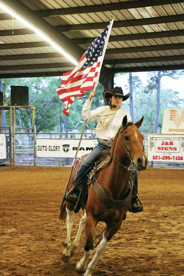 Kassidy Mabe runs the American flag as the national anthem is played at the start of the last year's Cleveland rodeo at Stancil Exposition Center. Photo: David Taylor