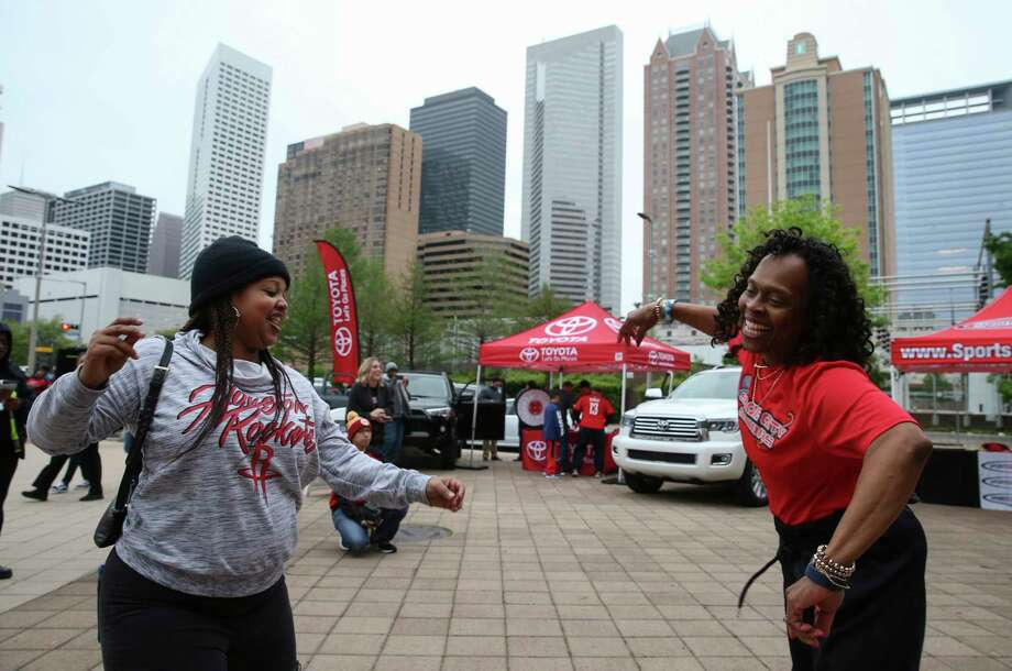Space City Senior dancer Michelle Cowherd, right, invites Rockets fan Delia Johnson to dance during a pregame performance by Houston-based band, The C.I.T.Y.. Photo: Yi-Chin Lee / © 2018 Houston Chronicle
