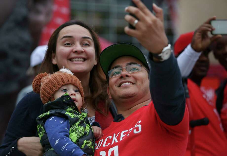 Veronica and Luis Guevara take a selfie with their son, Xavier, 9 months, who is bundled up in the cold weather outside Toyota Center. The Guevaras are NBA fans from El Salvador. They decided to come to their first Rockets game while on vacation in Houston. Photo: Yi-Chin Lee / © 2018 Houston Chronicle