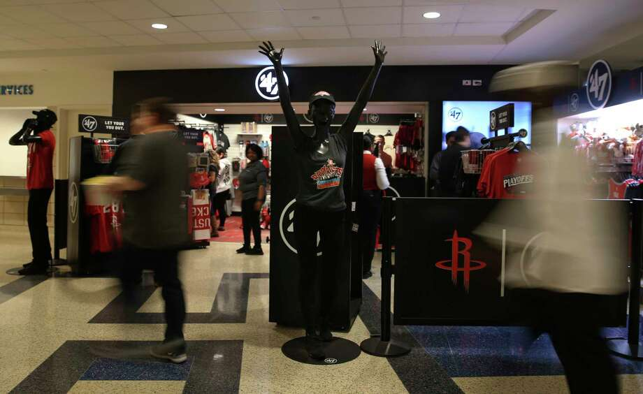 Rockets fans passing a cheerful mannequin in front of a pop-up team store on the Toyota Center concourse during halftime. Many fans purchased playoff merchandise at the store. Photo: Yi-Chin Lee / © 2018 Houston Chronicle