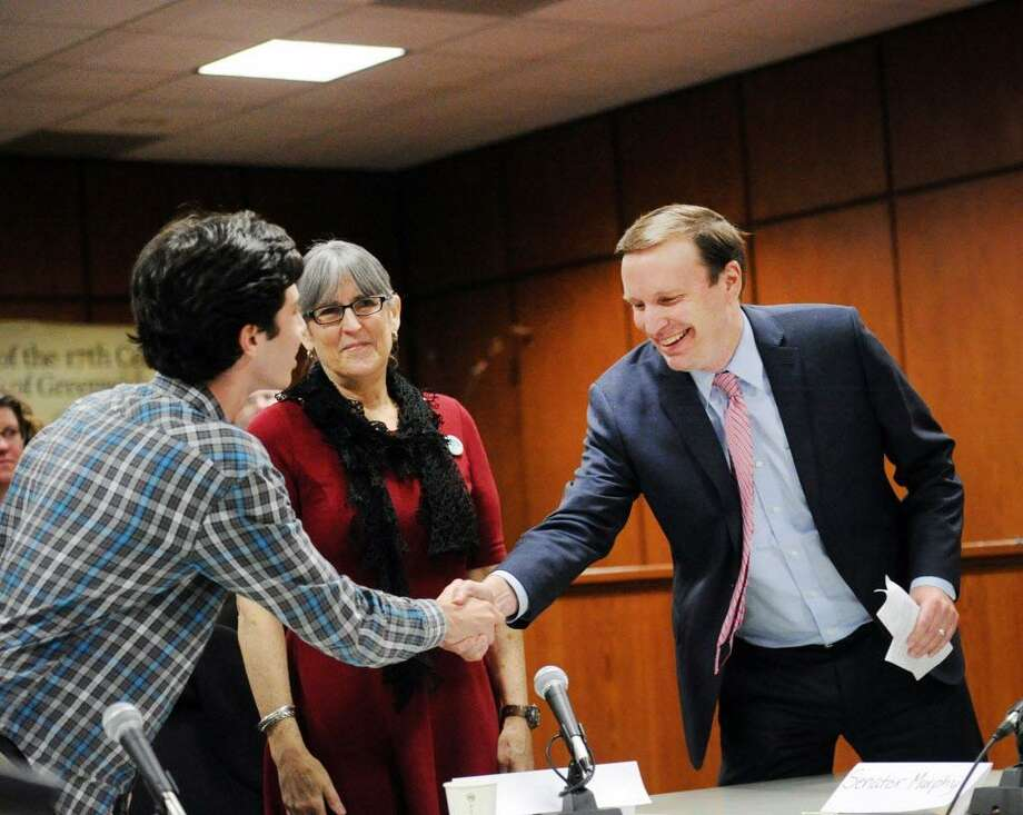 """Greenwich High School Student Body President, Greg Goldstein, left, shakes hands with U.S. Senator Chris Murphy of Connecticut just before the start of the public forum """"Roundtable Discussion on Gun Violence"""" at Greenwich Town Hall, Conn., Friday, March 2, 2018. At center is Carol Sutton, president of the Greenwich Education Association. Photo: Bob Luckey Jr. / Hearst Connecticut Media / Greenwich Time"""