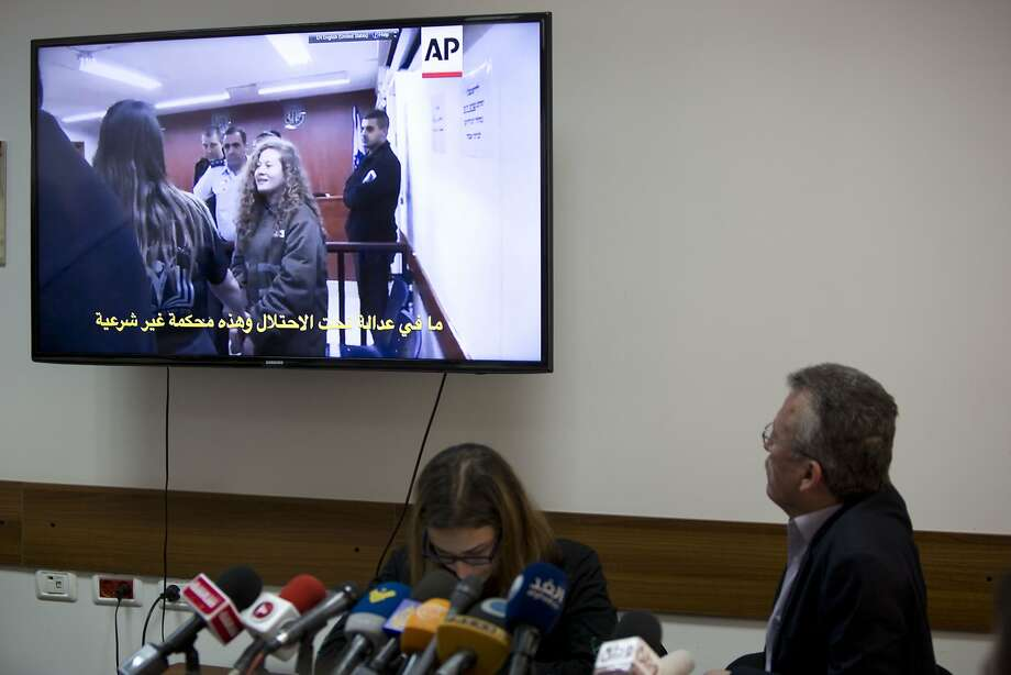 Bassem Tamimi (right) watches a video that shows his daughter, Ahed, in the West Bank city of Ramallah. Ahed Tamimi is serving an eight-month sentence for slapping two Israeli soldiers. Photo: Majdi Mohammed / Associated Press