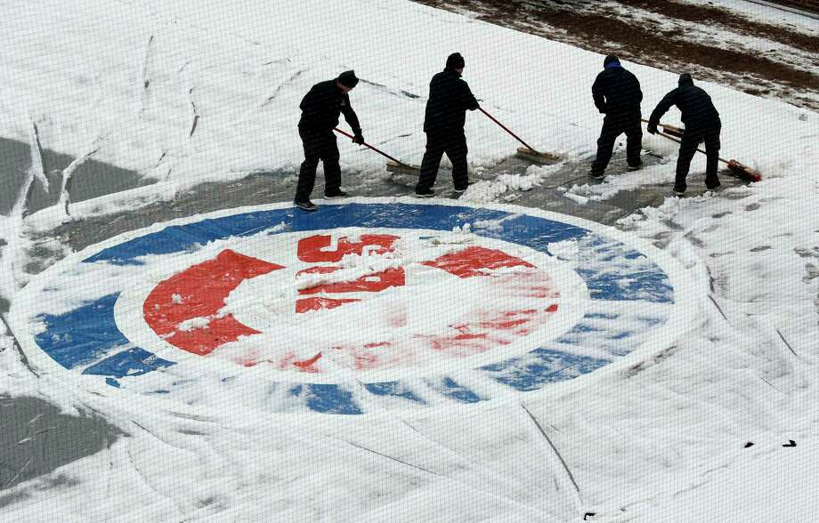Workers at Wrigley Field clear snow before the Chicago Cubs home-opener baseball game against the Pittsburgh Pirates, in Chicago. The Cubs' game against the Pirates was postponed a day because of persistent snow that covered much of Wrigley Field, creating a scene more reminiscent of December than April. (AP Photo/Nam Y. Huh) Photo: Nam Y. Huh, Associated Press / Copyright 2018 The Associated Press. All rights reserved.