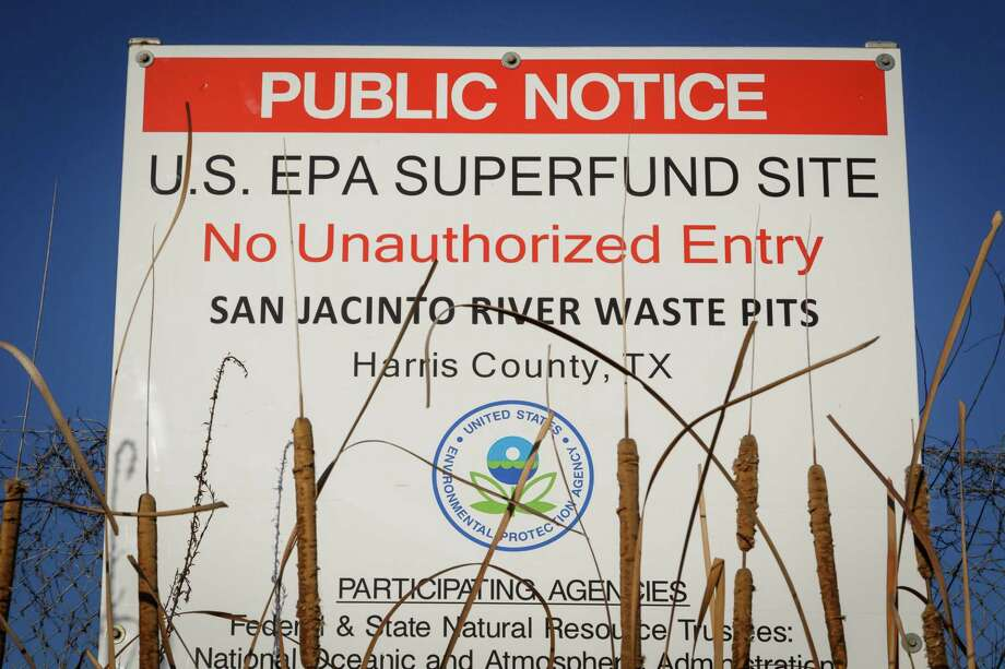 A sign warns the public about the EPA Superfund Site not to eat contaminated seafood caught from the water along I-10 near the San Jacinto River east of Houston, Tuesday, Dec. 17, 2013, in Channelview.  Texans Together, the Harris County Attorney's Office and residents are working together to spotlight the public health, fishing, and financial disaster that will result if a hurricane hits the San Jacinto Waste Pits, a highly vulnerable, toxic waste superfund site in the middle of the San Jacinto River and flows into Galveston Bay.  A recent government report reveals that the plastic lining placed in 2011 over the site's toxic wastes-- which the Waste Management and International Paper promised would protect the public for years, is eroding.  ( Michael Paulsen / Houston Chronicle ) Photo: Michael Paulsen, Staff / Houston Chronicle / Internal