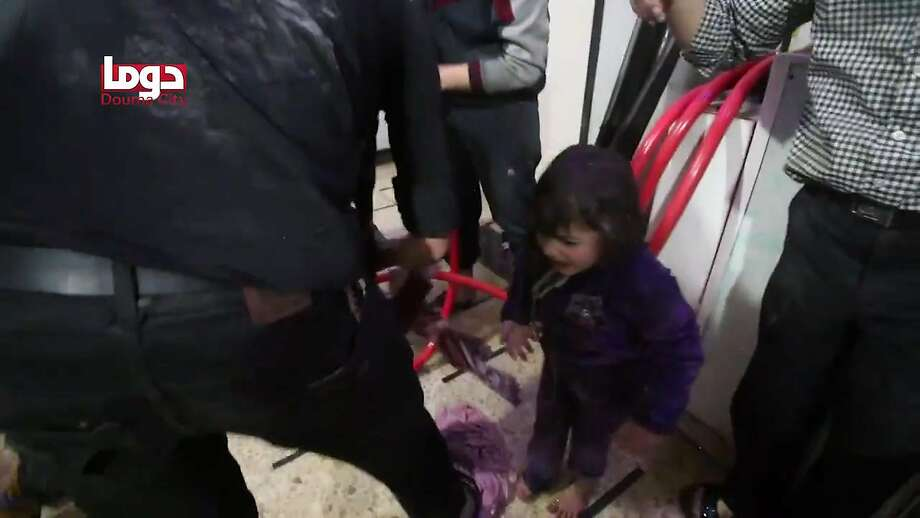 An image from a video released by the Douma City Coordination Committee shows a girl being sprayed with water Saturday following an alleged chemical attack on the rebel-held town. Photo: AFP / Getty Images