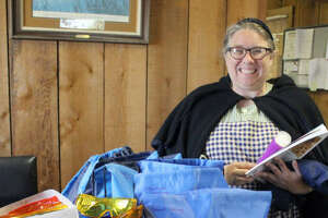 George Ranch Historical Park Director of Programs Krystal Willeby dressed in an 1860s-era costume displays some Sensory-Friendly Day components. The kits in the blue smiley-faced bags include lap pads, lavender lotion, stress balls, fidget spinners, crayons, coloring books and picture books. Headphones and colored glasses will be available for check-out on the April 15 Sensory-Friendly Day. These were made possible by a grant from Fort Bend Cares and will be provided to help families with children and adults with Autism Spectrum Disorders and other sensory and developmental challenges to explore the park in a safe, structured and enjoyable manner.