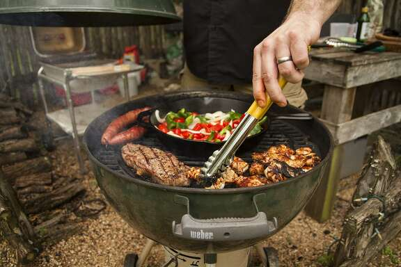 Chuck Blount works the grill that contains a sausage link, steak, grilled vegetable medley and spicy chicken wings.