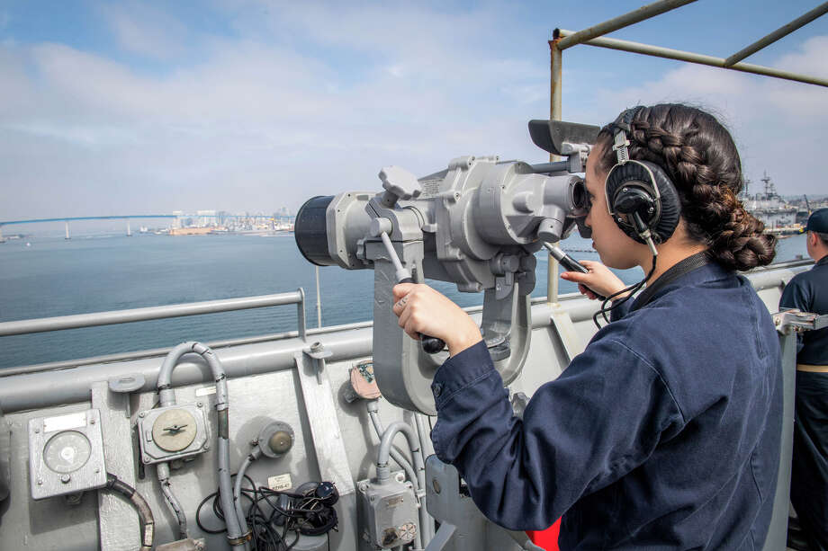 "Operations Specialist 2nd Class Kerri C. Barriera, from Montgomery, looks through the ""Big Eyes"" as the Harpers Ferry-class amphibious dock landing ship USS Pearl Harbor (LSD 52) departs San Diego. Pearl Harbor is currently underway off the coast of Southern California conducting routine training operations. (U.S. Navy photo by Mass Communication Specialist 3rd Class Kelsey J. Hockenberger/Released)"