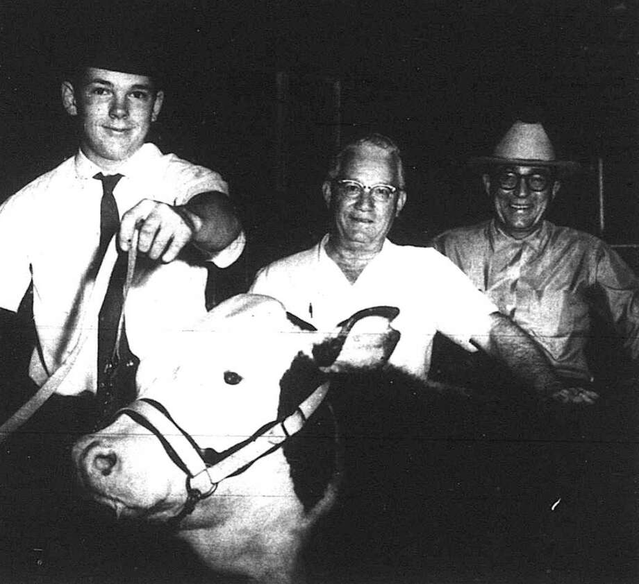 "Pictured are R. D. Simonton and Frank Powell representing the Conroe National Bank, with ""Jake"" the Grand Champion Steer of the 1965 Junior Livestock Show at Cow Palace. He was shown by Martin Weldon of Willis FFA. The steer brought in a record over the previous year."